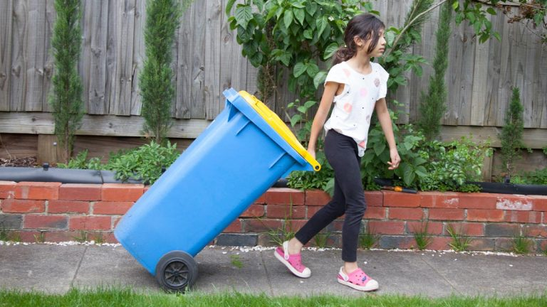 Girl pulling a trash can