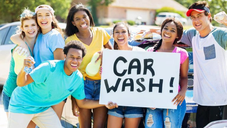 Teens with sign for car wash
