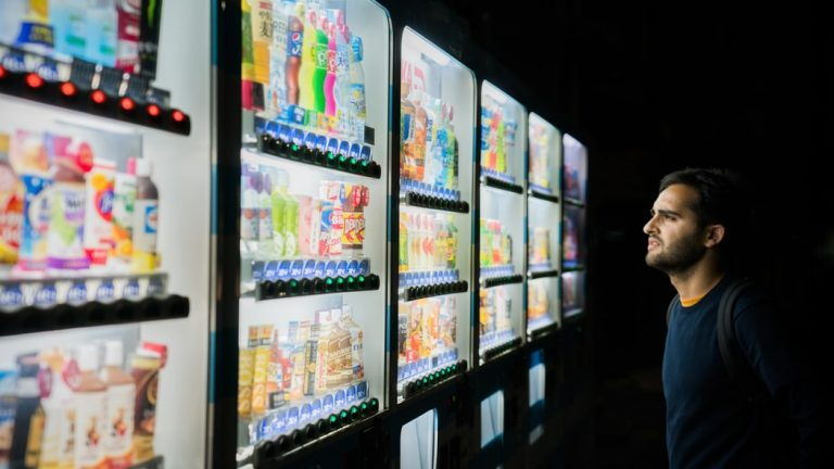 man looking at lines of vending machines