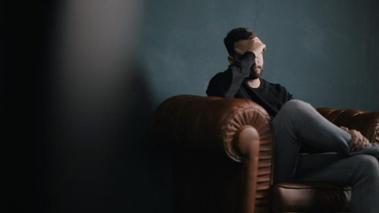 man sitting in chair looking stressed