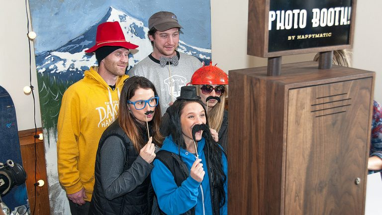 people posing at a photo booth with mountain thenme